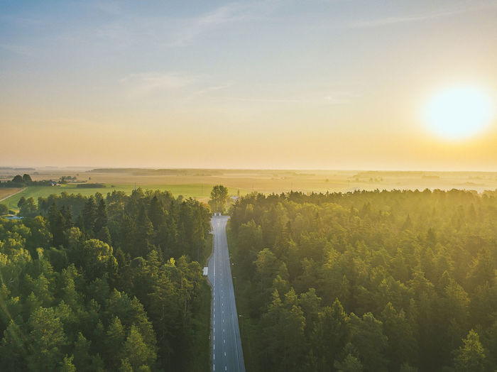 Scenic view of road amidst green land against sky during sunset