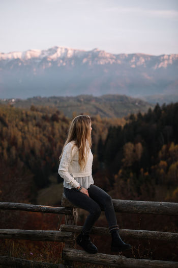 Beautiful blonde woman relaxing on the fence in the mountains at sunset. vacation travel,concept.