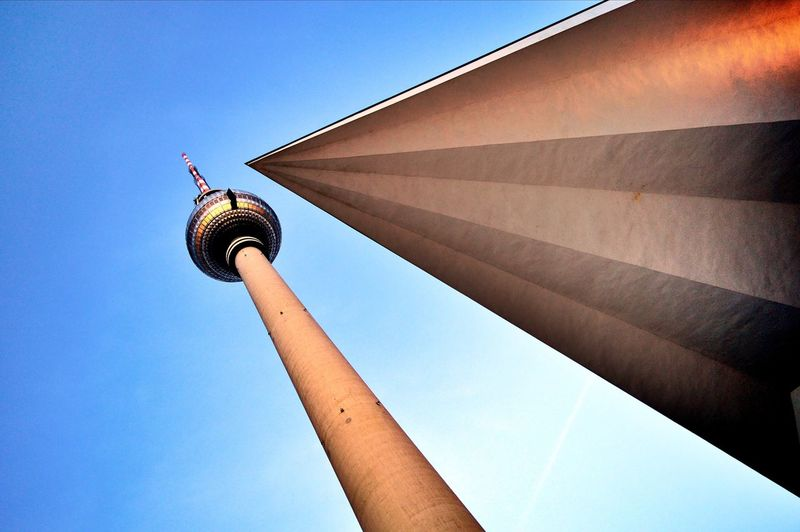 Low angle view of fernsehturm amidst clear blue sky