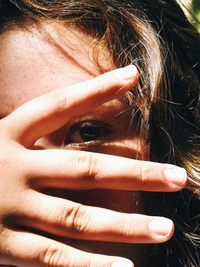 Close-up portrait of girl covering face with hand