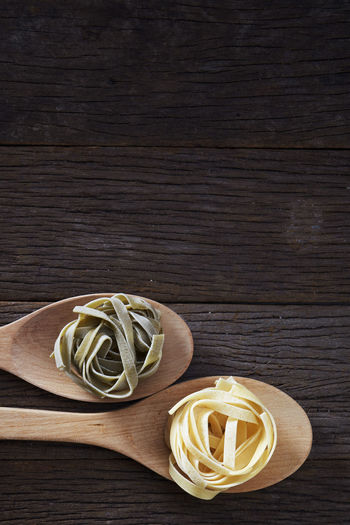 Close-up of tagliatelle pasta in wooden spoons on table