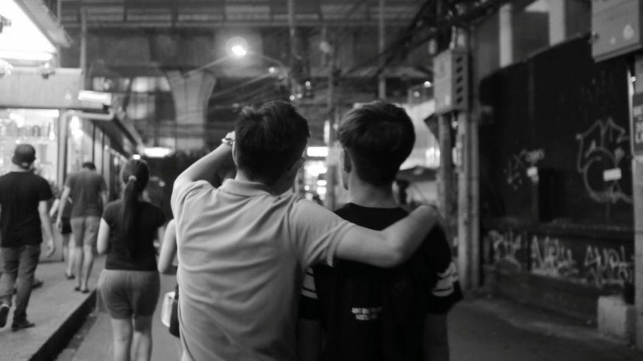 Rear view of male friends walking on street in city