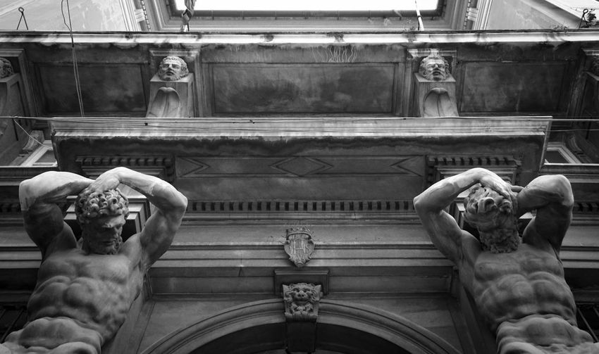 Facade. Two strong men holding the main door. Sony Sonyalpha Sony A6000 Photographer Photo Photography EyeEm Best Shots EyeEm Selects Windows Streetphotography Streets Blackandwhite Architecture Built Structure No People Sculpture Statue Human Representation Façade Facades Strong Man Genova Genova ♥ Italy Architecture_collection Architectural Feature Arch Via Garibaldi,genova Architectural Design Architecture And Art