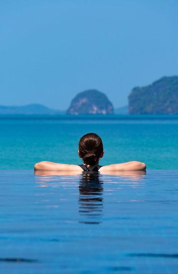 Portrait of man swimming in pool against sea