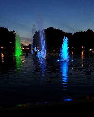 Silhouette people on illuminated bridge against sky at night