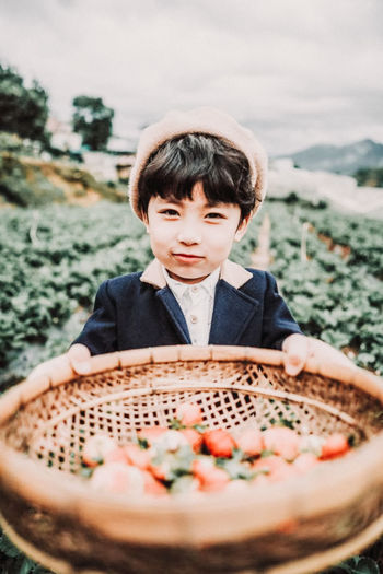 Portrait of boy holding basket with strawberries at farm
