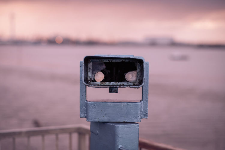 Close-Up Of Coin-Operated Binoculars By Sea During Sunset