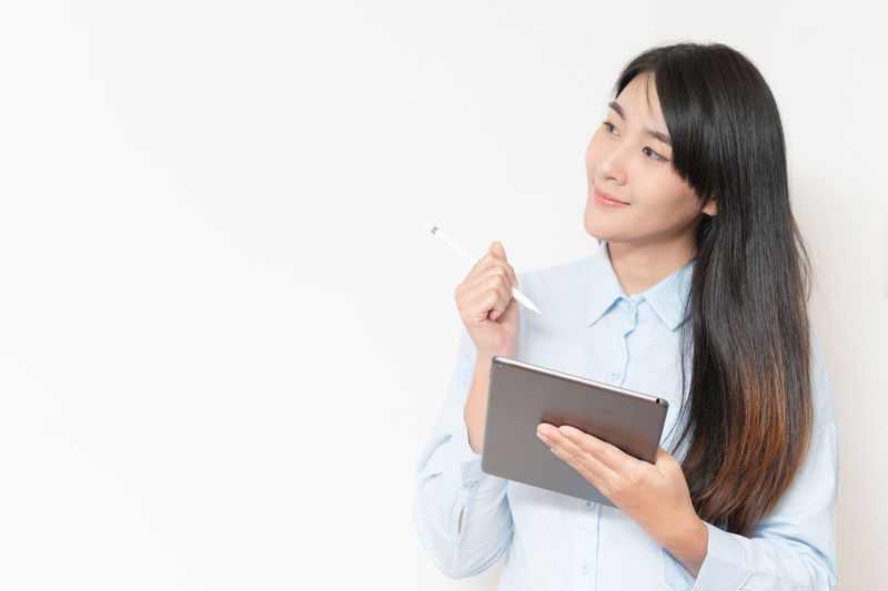 Young woman using phone while standing against white background