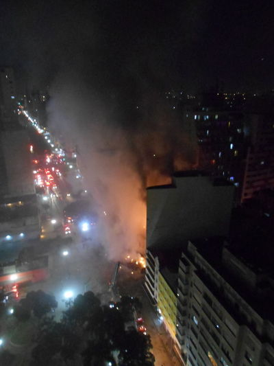 Inner City Calamity in downtown São Paulo at Largo do Paissandú; 3 am May 1, 2018. The abandoned former Federal Police steel and glass skyscraper, which had been invaded by street people, imploded this early morning and the neighboring building has caught on fire as well. City City Life Destruction Destruction Can Be Beautiful Inner City Largo Do Paissandu Night Photography Susan A. Case Sabir Unretouched Photography Building Fire Building Implosion Burning Building Controlled Chaos Dangerous Situation Downtown São Paulo High Angle View Illuminated Implosion Night No People Responsiveness Smoke - Physical Structure Unexpected Event Urban Photography Urban Strife