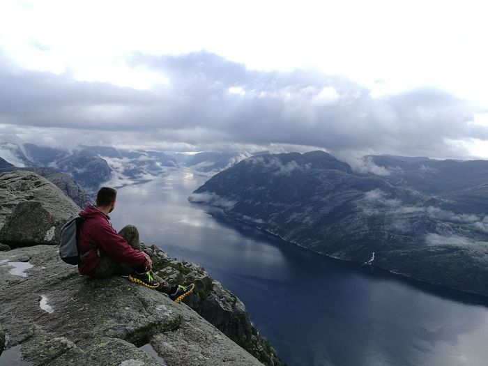 Male hiker sitting on cliff against valley
