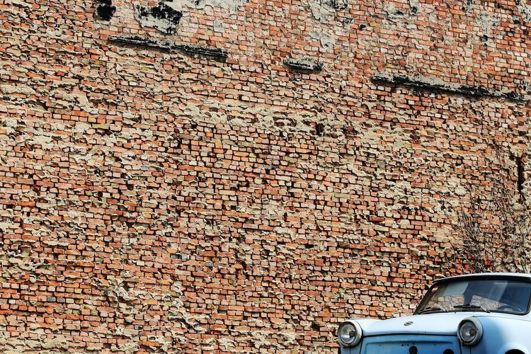 Car parked against brick wall
