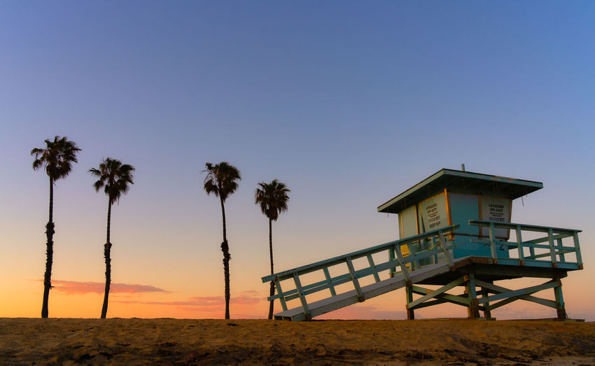 Lifeguard hut on beach against clear sky during sunset