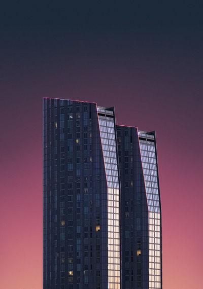 Low angle view of modern building against sky at dusk