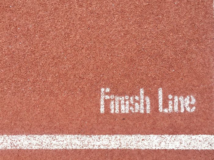Top view of finish line on the running track Healthy Lifestyle Nobody Sport Symbol Abstract Accomplishment Successful Letter Text Western Script Communication No People Running Track Track And Field Day High Angle View Sport Sign White Color Full Frame Close-up Outdoors Road Pattern Symbol Sunlight Brown