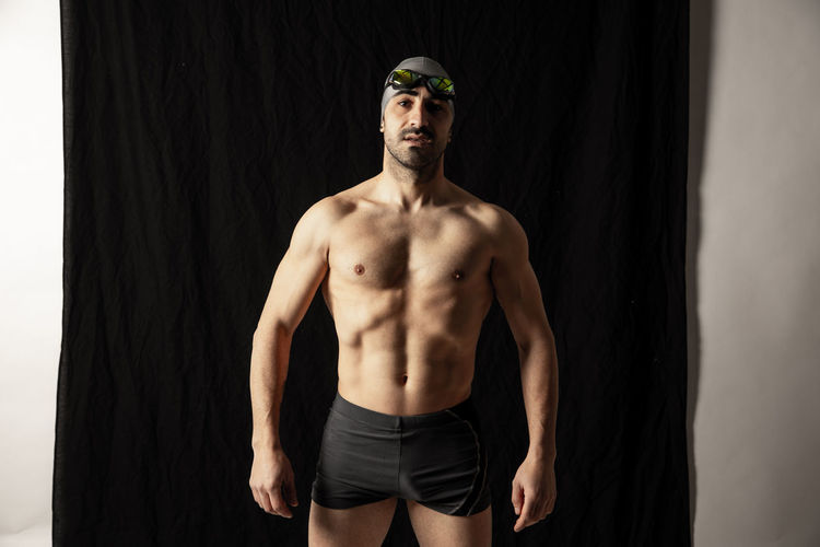 Portrait of shirtless man standing against wall