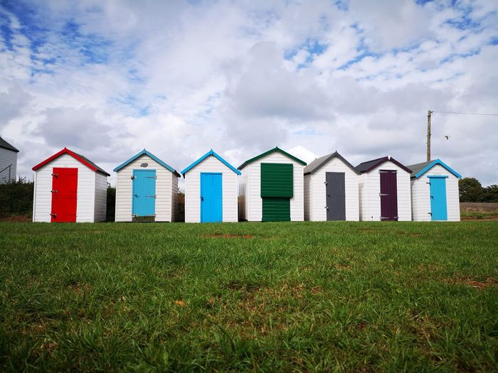 Beach huts on grassy field against cloudy sky