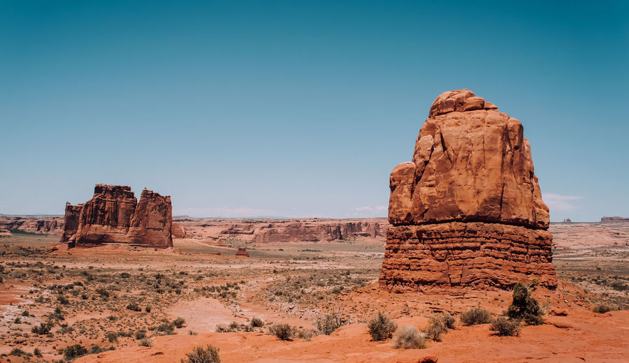 Scenic view of rock formations and landscape against blue sky