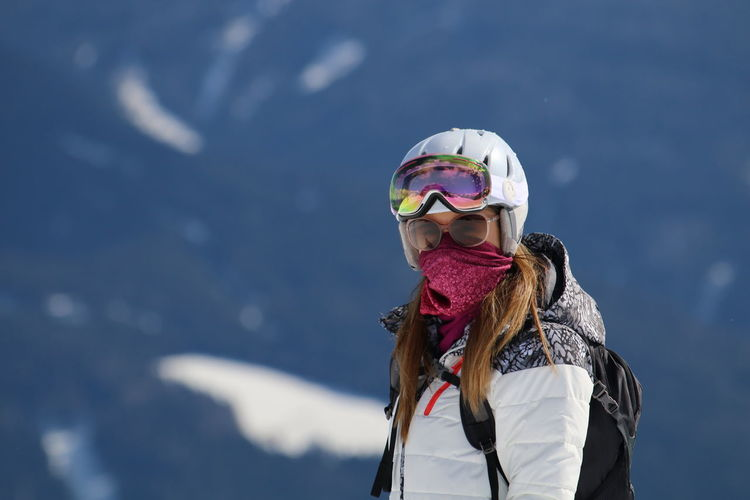 Portrait of young woman wearing skiing helmet during winter