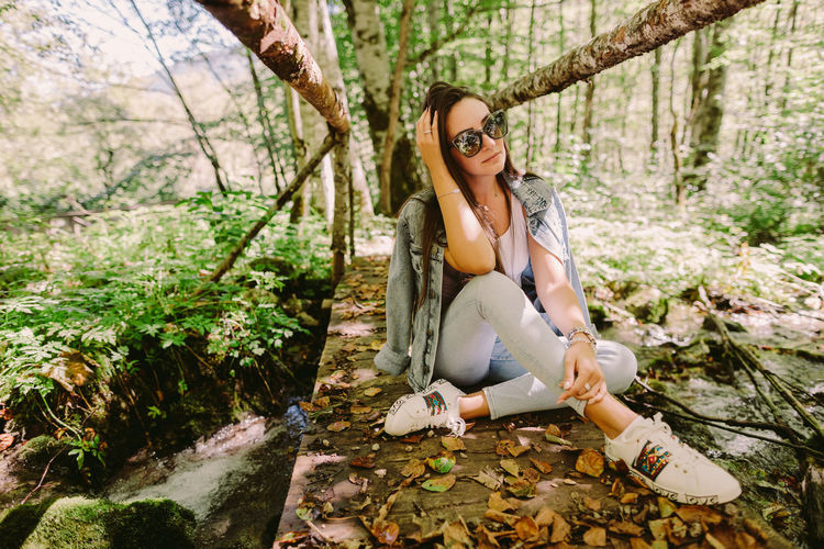 Full length of woman sitting on land in forest