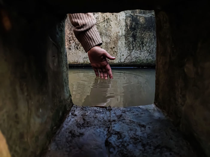 The reflection of a girl's hand fellon a water-filled cistern.