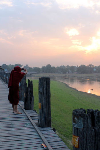 U-BEIN BRIDGE/AMARAPURA, MYANMAR JAN 22, 2016: Buddhist monk capturing the sunrise over the Taungthaman lake with his mobile phone. Amarapura Beauty In Nature Bridge Buddhism Buddhist Cloud - Sky Lake Mandalay Men Monk  Nature One Person Outdoors People Real People Rear View Religion Scenics Sky Sunrise The Photojournalist - 2017 EyeEm Awards Tradition Travel Destinations U-bein Bridge,Myanmar Wooden Summer Exploratorium A New Beginning