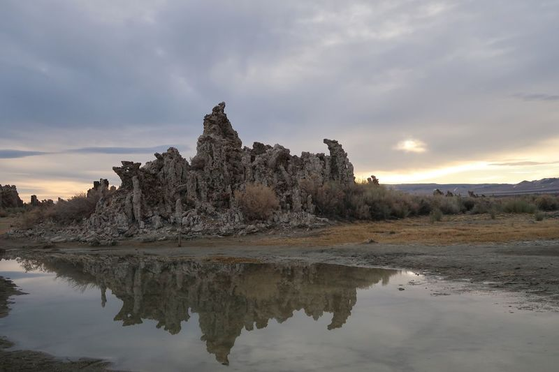 Landscape of large tufa formations reflected in Mono Lake Tufa Mono Lake Sky Water Reflection Cloud - Sky Tree Nature Tranquility Tranquil Scene Scenics - Nature No People Land Lake Environment Outdoors Landscape Beauty In Nature Travel Destinations