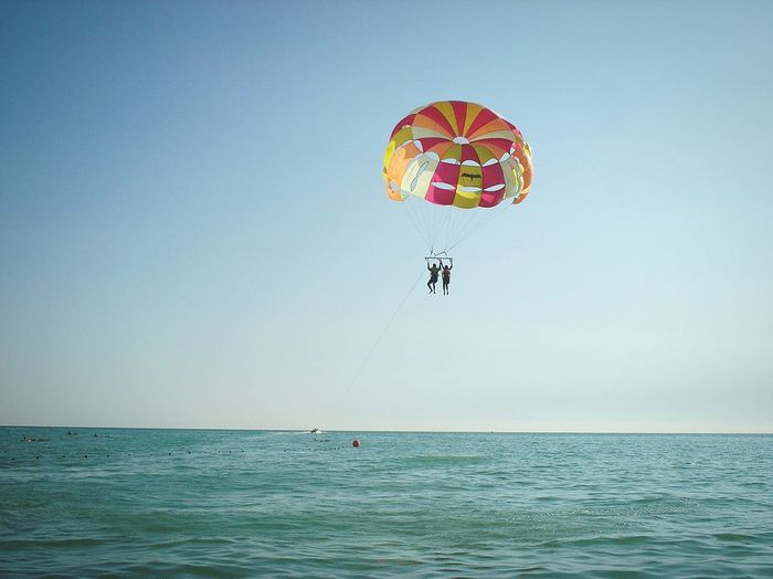 Multi Colored Parachute Flying Over Sea