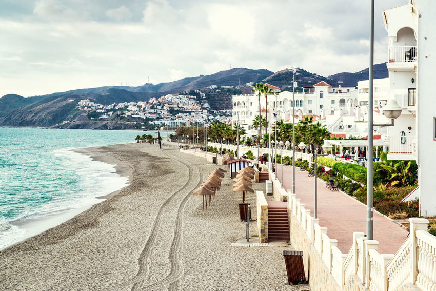 Empty beach. Nerja, Spain Andalucía Beach Beach Umbrellas Cloudy Sky Coast Coastline Costa Del Sol Europe Holiday Houses Landscape Mediterranean Sea Mountain Nature Nerja Outdoors Parasols Resort Sand Seaside SPAIN Straw Parasol Town Tropical Climate Vacations