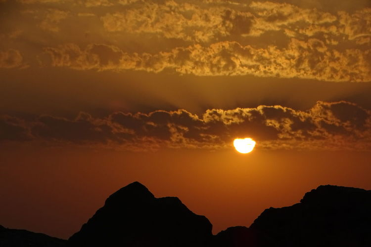 Scenic view of silhouette mountain against orange sky