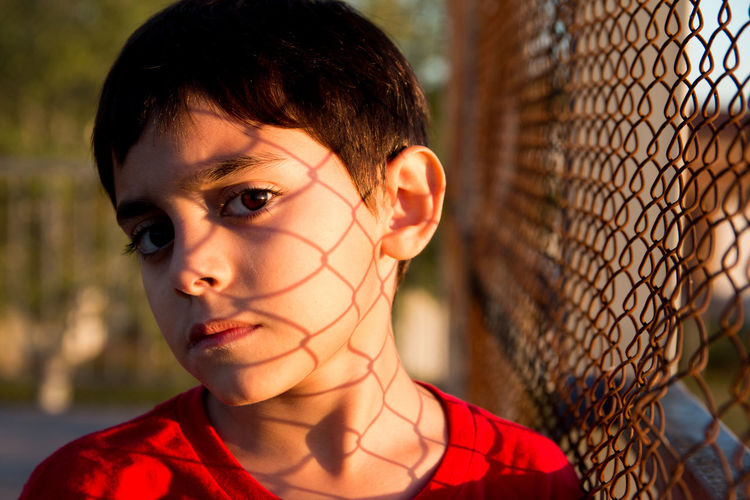 Close-up of portrait of boy with chainlink fence shadow on face