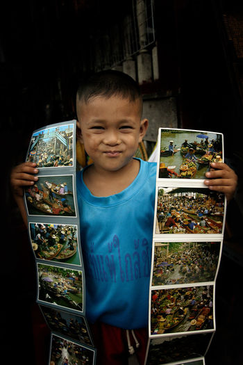 A little boy selling postcard on street Asian  Business Market Postcard Travel Vacations Young Boys Childhood Cultures Day Indoors  One Person People Real People Sell Street Tourism Vendor
