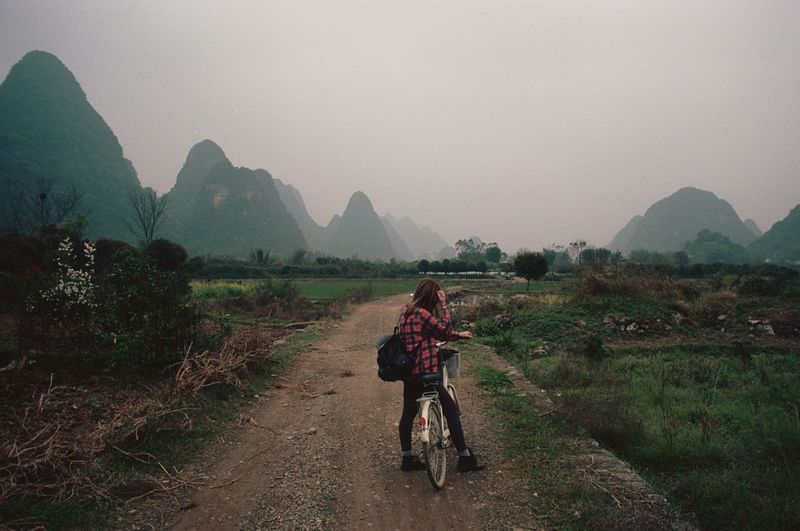 REAR VIEW OF YOUNG WOMAN WITH BICYCLE ON DIRT ROAD