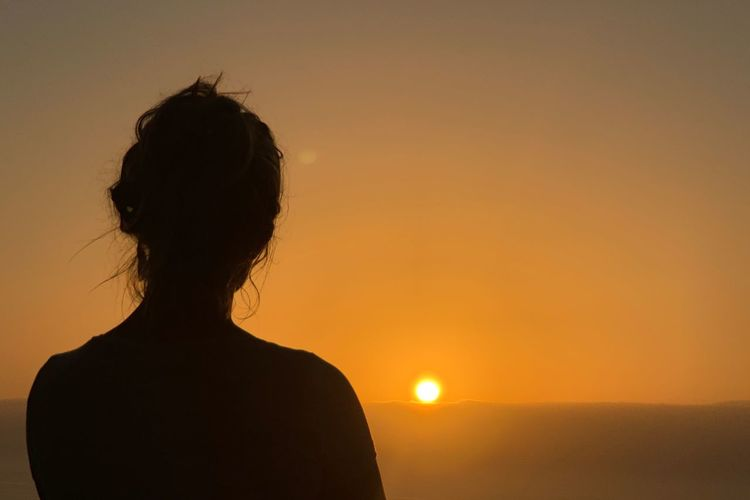 Rear view of silhouette woman standing against sky at sunset