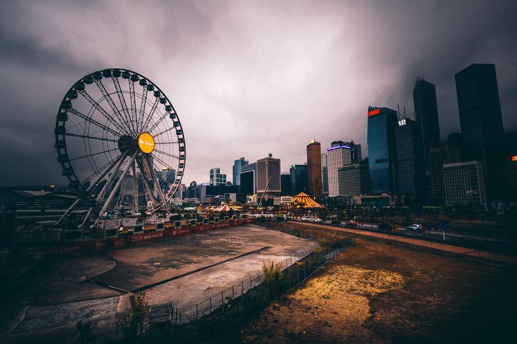 Ferris wheel in city against sky at dusk