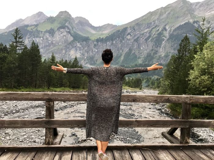 Rear View Of Woman With Arms Outstretched Standing On Bridge