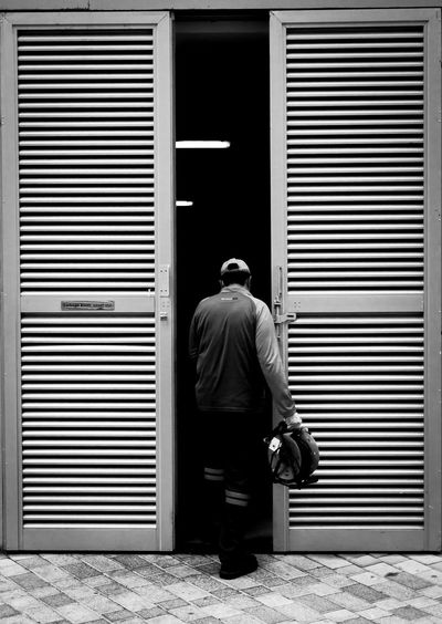 Rear view of man standing against closed shutter
