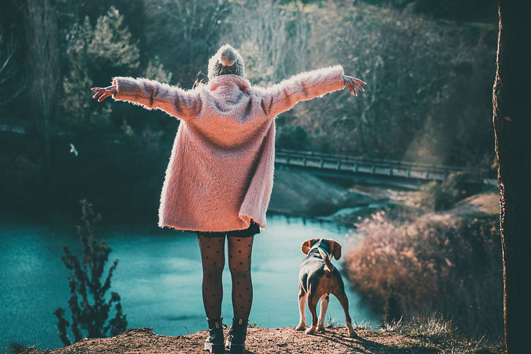 Rear view of woman with dog standing at lake