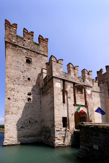 The entrance to the 12th century fortification of Scaliger Castle in Sirmione on lake Garda, Italy Historical Building Travel Photography Arch Architecture Building Building Exterior Built Structure Castle Clear Sky Day Europe Fort Fortification History Moat Nature No People Old Outdoors Sky The Past Tourism Travel Destination Water Waterfront