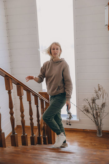 Full length of woman standing on steps at home