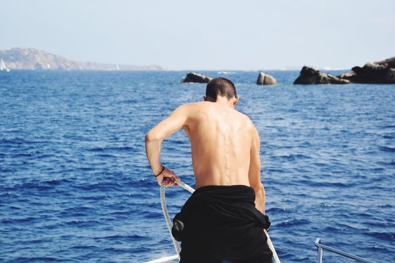 Rear view of shirtless man on boat in sea against sky