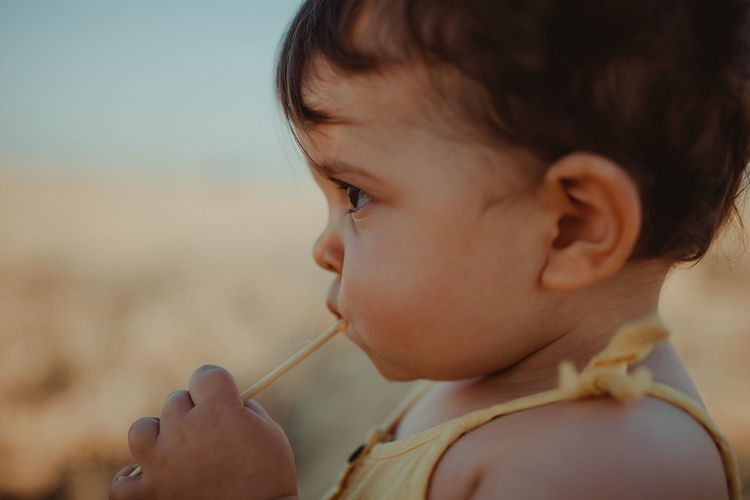 Close-up of baby girl eating candy outdoors
