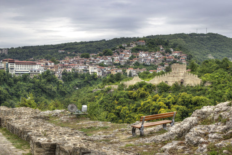 Bench with view of residential district on mountain with bench in foreground against cloudy sky