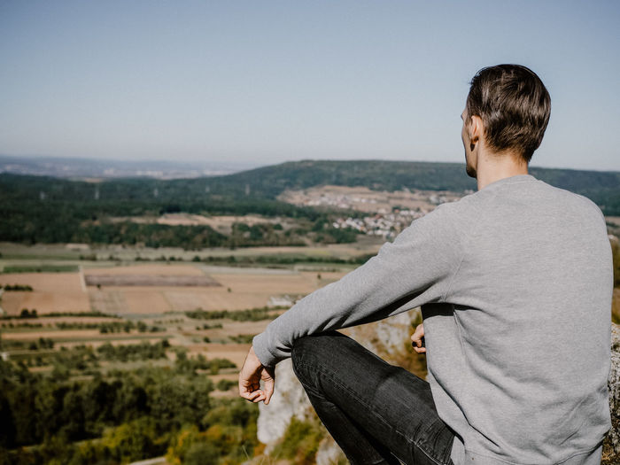 Rear view of man sitting on cliff against sky