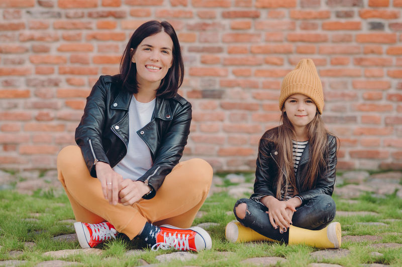 Portrait of smiling mother with daughter sitting on land against brick wall