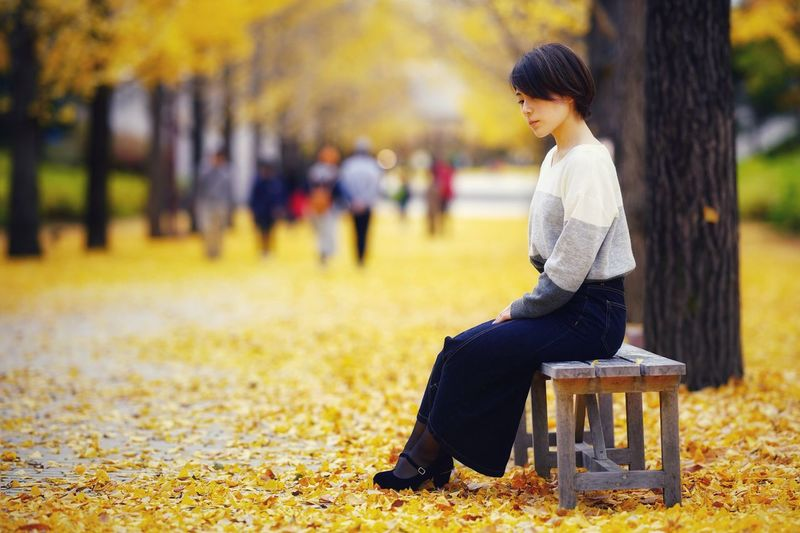 Side view of senior man sitting on seat in park