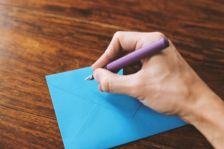 Cropped image of man writing on blue envelope