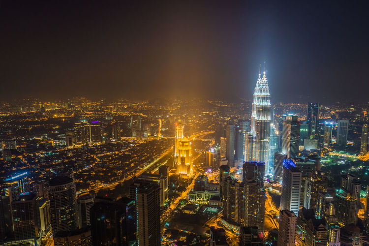 Aerial view of illuminated city buildings at night