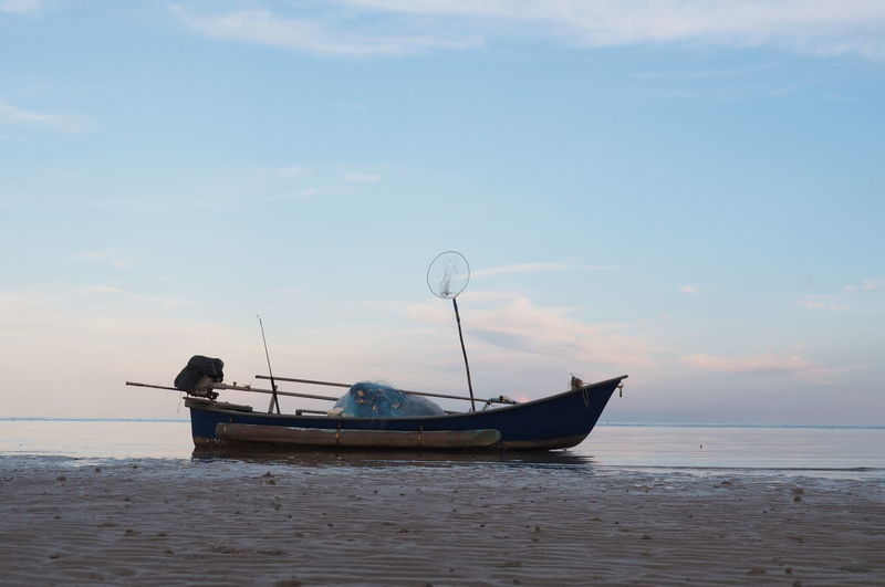 Boat on sea against sky during sunset