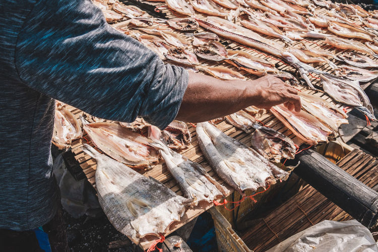 Midsection of man selling fish on market stall