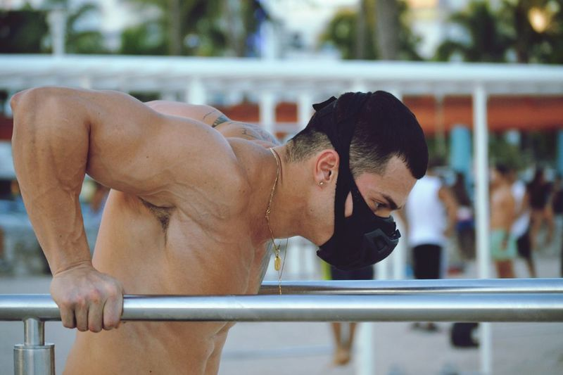 Side view of man exercising on railing